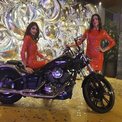 Черный Harley-Davidson и хостес девушки в красном, идеальное сочетание